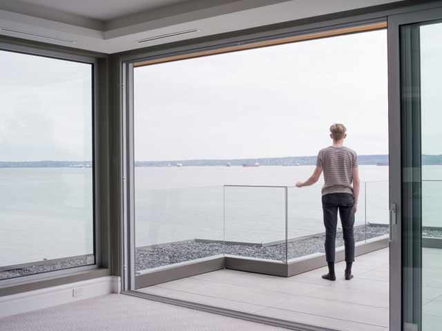 Man standing on patio with glass railing overlooking a large body of water.
